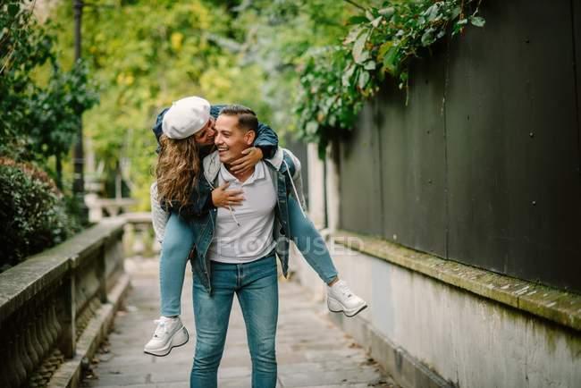 Contenu femme en vêtements décontractés assis sur le dos et embrasser homme heureux marchant sur une petite ruelle avec des plantes vertes sur fond flou — Photo de stock
