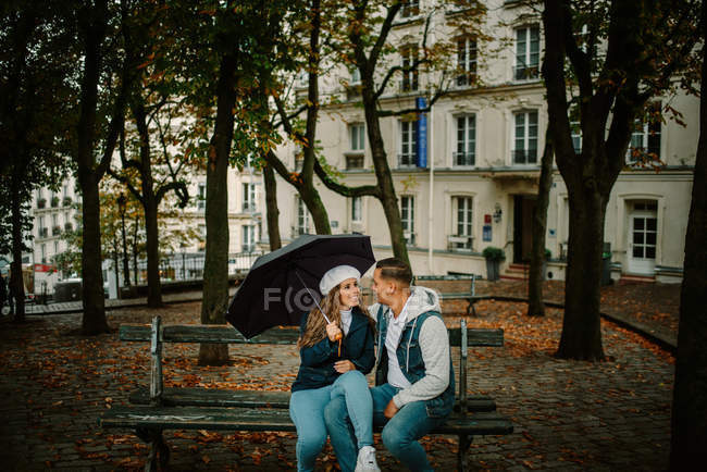 Content woman in casual clothing sitting with young man on bench of beautiful neighbourhood holding an umbrella — Stock Photo