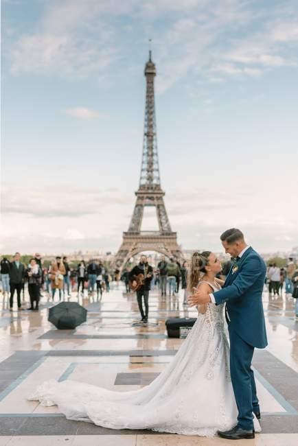 Гриб в синьому костюмі і наречена в білій весільній сукні, які повільно танцюють посміхаються і дивляться один на одного з Ейфелевою вежею на задньому плані в Парижі. — стокове фото