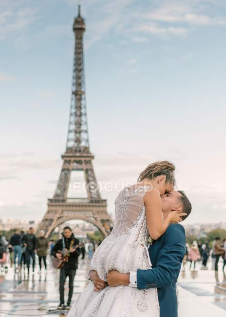 Groom in blue suit and bride in white wedding gown kissing passionately with Eiffel Tower on background at Paris — Stock Photo