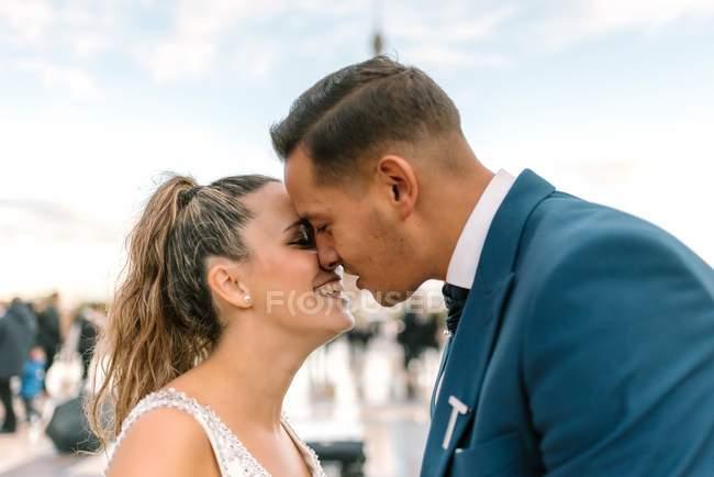 Гриб в синьому костюмі і наречена в білій весільній сукні цілуються пристрасно з Ейфелевою вежею на задньому плані в Парижі. — стокове фото