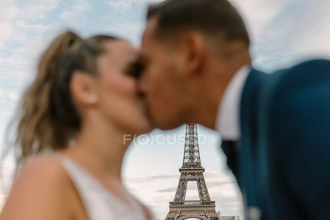 Out of focus groom in blue suit and bride in white wedding gown kissing passionately with Eiffel Tower on background at Paris — Stock Photo