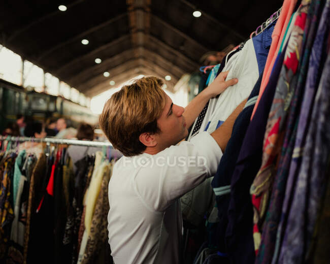 Side view of young guy in white shirt selecting new outfit on clothes rail on railway station market — Stock Photo
