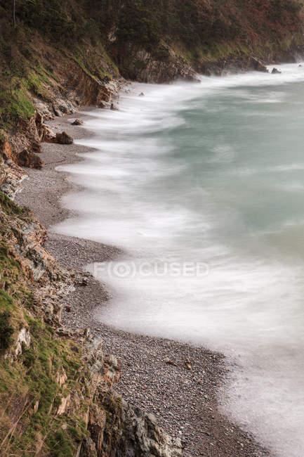 Von oben malerische friedliche Küste mit ruhigen azurblauen Wellen im Licht der untergehenden Sonne am felsigen Strand von Silence O Gaviero — Stockfoto