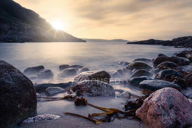 Туманная поверхность моря с большими скалами на песчаном пляже и горы на восходе солнца на пляже Портоново в Италии — стоковое фото