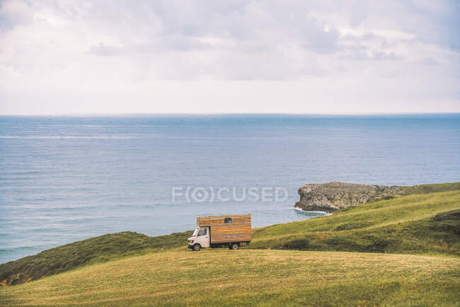 Golden field on hill and small cargo truck with blue sea and cloudy sky on background at Comillas Cantabria at Spain — Stock Photo
