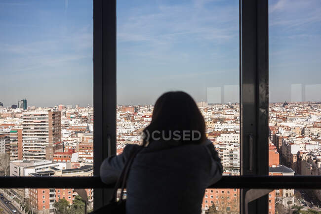 Anonymous woman looking out balcony window — Stock Photo