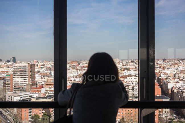 Mulher anônima olhando para a janela da varanda — Fotografia de Stock