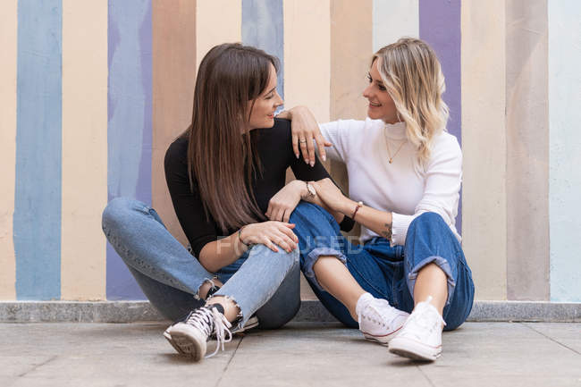 Smiling positive elegant women leaning on each other while sitting close on sidewalk near striped street wall looking at each other — Stock Photo