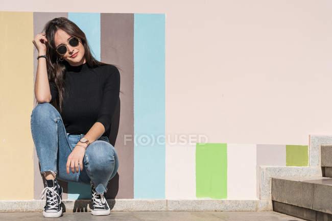Красивая женщина в стильном наряде и солнцезащитных очках опирается на окрашенную городскую стену, сидя одна в солнечный день — стоковое фото