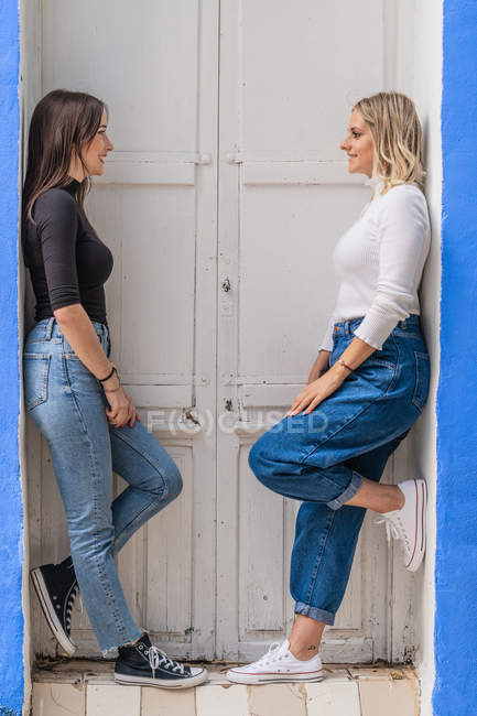Side view of happy gentle caring girlfriends in stylish outfit standing near door looking at each other — Stock Photo