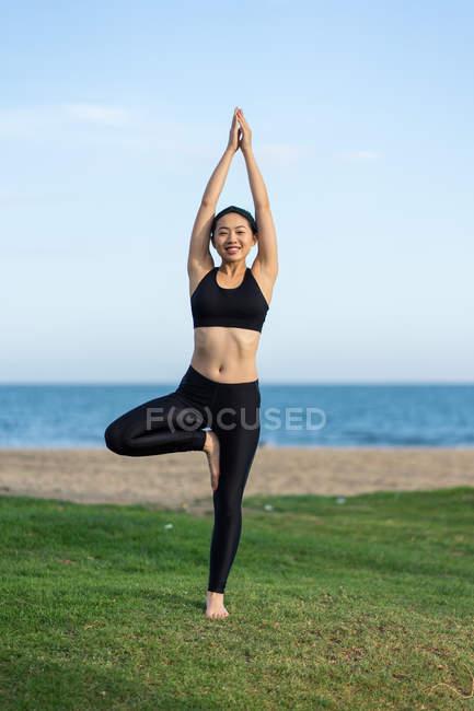Молодая стройная женщина в черном топе и ногах, стоящая в позе дерева на зеленой траве, практикуя йогу на пляже — стоковое фото