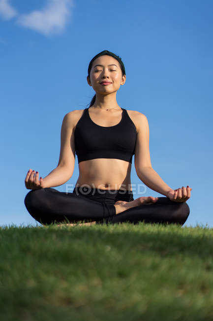 Young woman in black top and leggings sitting on lotus position on green grass with closed eyes while meditating at the beach — Stock Photo