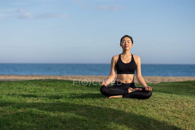 Woman in black top and leggings sitting on lotus position on green grass with closed eyes while meditating at the beach — Stock Photo
