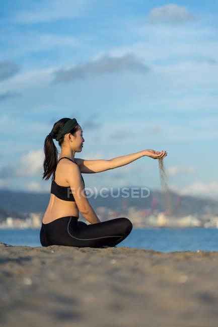 Женщина в черном одеянии, сидящая на пляже со скрещенными ногами и посыпающая песком пальцы во время отдыха после тренировки — стоковое фото