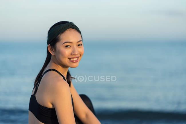 Вид сбоку женщины в черном платье, сидящей со скрещенными ногами на пляже, отдыхающей после тренировки, глядя в камеру — стоковое фото