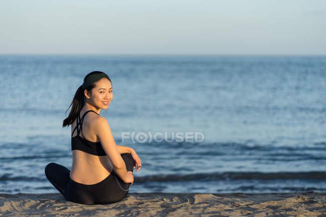 Вид сбоку улыбающейся женщины в черном костюме, сидящей со скрещенными ногами на пляже, отдыхающей после тренировки, глядя в камеру — стоковое фото