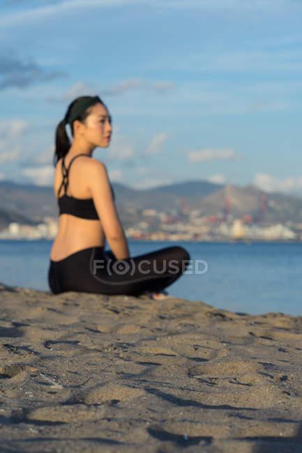 Вид сбоку на красивую женщину в черном платье, сидящую со скрещенными ногами на пляже, отдыхающую после тренировки — стоковое фото