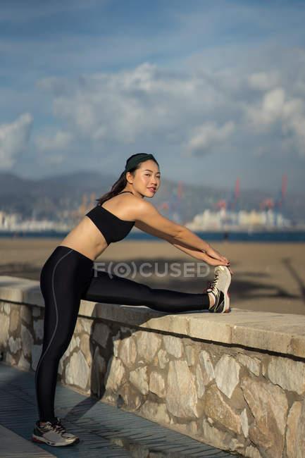 Vista lateral da mulher asiática em cima preto e leggings fazendo alongamento exercício enquanto está ao lado de cerca de pedra à beira-mar — Fotografia de Stock