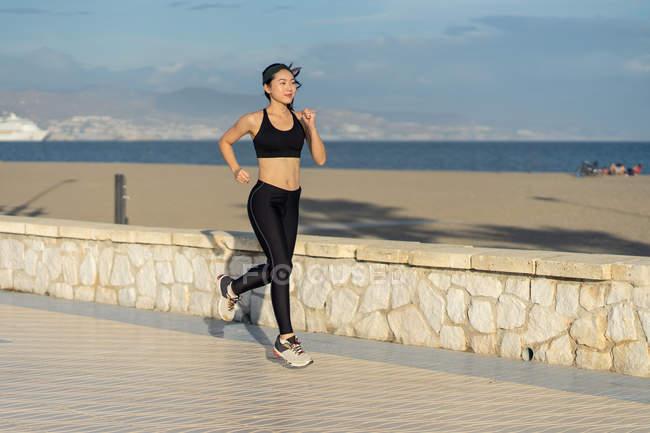 Женщина в активном черном одеянии и бегущая вдоль скального забора вдоль пляжа по пустому берегу моря — стоковое фото