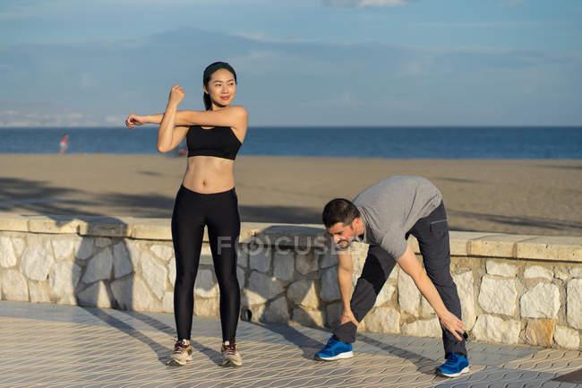 Paar steht in Sportkleidung mit blauem Meer und Himmel vor verschwommenem Hintergrund — Stockfoto