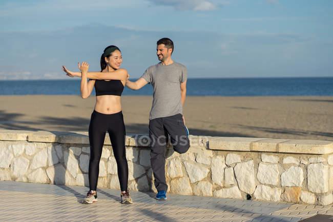 Пара, стоящая на одной ноге, держа друг друга в спортивной одежде с голубыми морями и небом на размытом фоне — стоковое фото