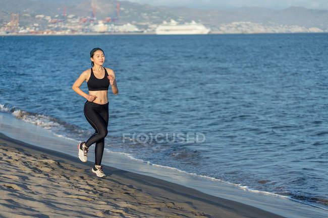 Atleta joven motivada con traje negro activo y zapatillas que juegan a lo largo de la arena de mar vacía. - foto de stock