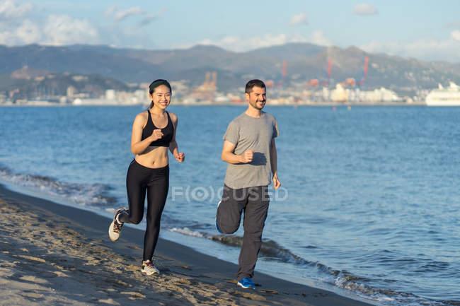 Пара в спортивной одежде улыбается во время пробежки по песчаной стороне океана с городом на противоположном берегу на размытом фоне — стоковое фото