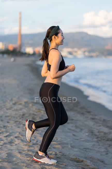 Вид сбоку мотивированной молодой спортсменки в активной черной одежде и бегущей по песчаному пустому берегу — стоковое фото