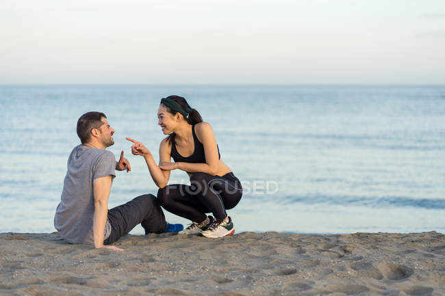 Cheerful young multiracial couple in sportswear sitting on sandy beach while resting after training and enjoying time together — Stock Photo