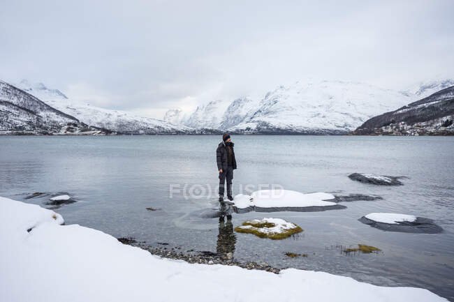 Solitary tourist on fjord shore against snowy hills in cold overcast weather — Stock Photo