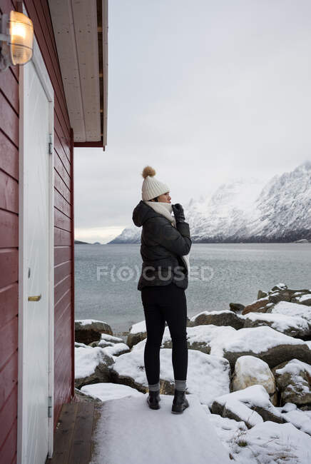 Solitary woman on rocky shore against tranquil lake and snowy mo — Stock Photo