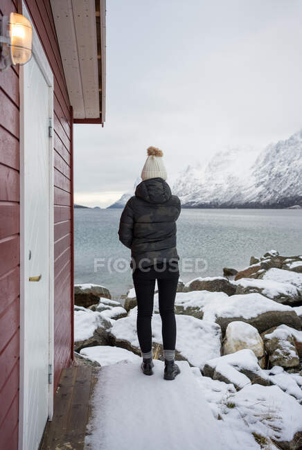 Solitary woman on rocky shore against tranquil lake and snowy mountains in cold day — Stock Photo