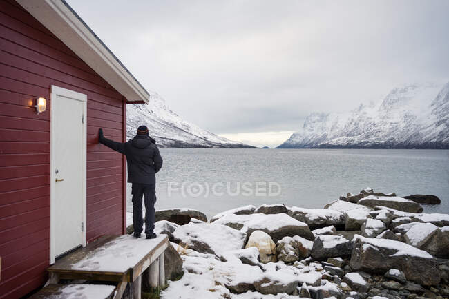 Solitary man on rocky shore against tranquil lake and snowy moun — Stock Photo