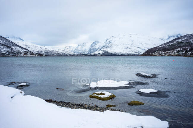 Tranquil lake against snowy hills in cold overcast weather — Stock Photo