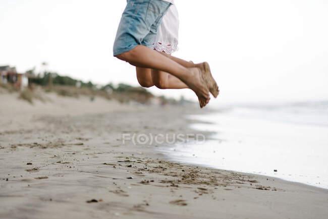 Cultiver jambes nues de couple de bonheur en vacances en été porter sauter sur le rivage sablonneux vide — Photo de stock