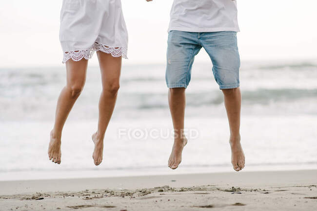 Crop barefoot legs of happiness couple on vacation in summer wear jumping on sandy empty seashore — Stock Photo