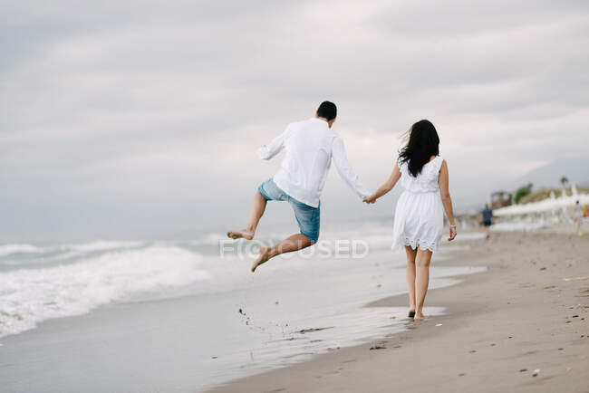 Back view of happy couple on vacation in summer jumping on sandy empty seashore — Stock Photo
