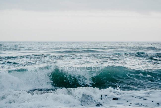Mer sans bornes de couleur turquoise avec vagues et mousse blanche borderline avec ciel bleu clair — Photo de stock