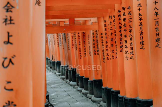 Point de repère fascinant avec des portes rouges occupées de symboles kanji japonais sur un sentier rocailleux au temple Fushimi Inari à Kyoto, Japon — Photo de stock