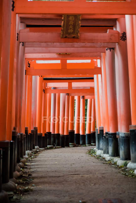 Intriguing landmark with red gates occupied of Japanese kanji symbols on rocked path at Fushimi Inari temple at Kyoto, Japan — Stock Photo