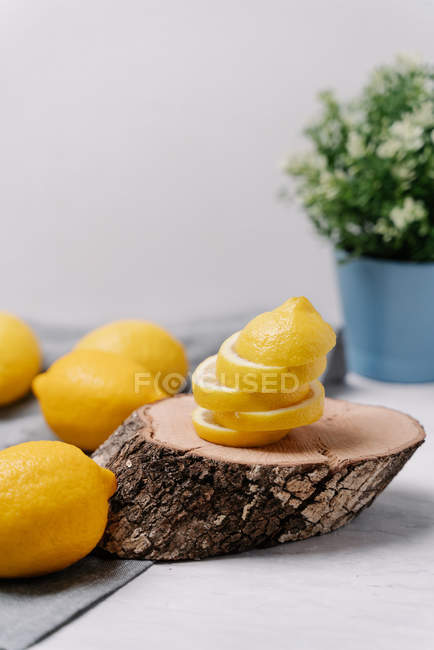 Close-up of pieces of fresh lemons placed on wooden piece on blurred background — стоковое фото