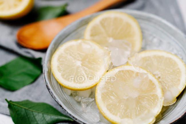 Desde arriba trozos de limón fresco en un tazón con hielo decorado con hojas verdes sobre fondo borroso - foto de stock