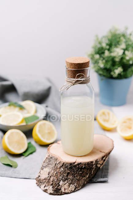 Бутылка лимонада, сервируемая на деревянном куске, украшенном выжатыми лимонами на столе — стоковое фото