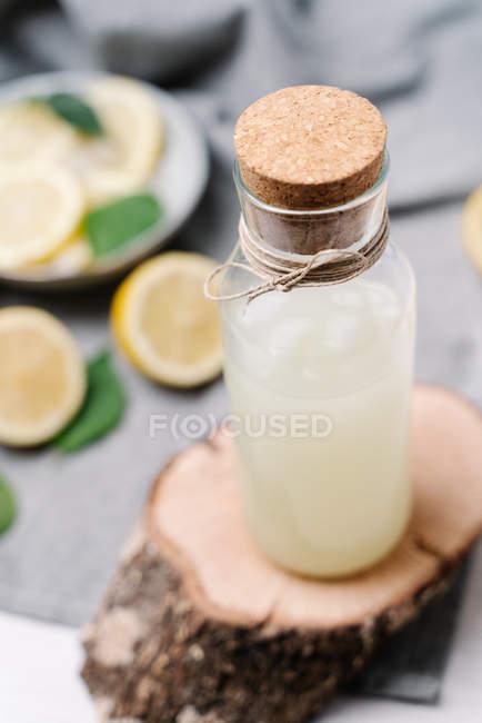 Botella de limonada que sirve en pieza de madera decorada con limones exprimidos en la mesa - foto de stock