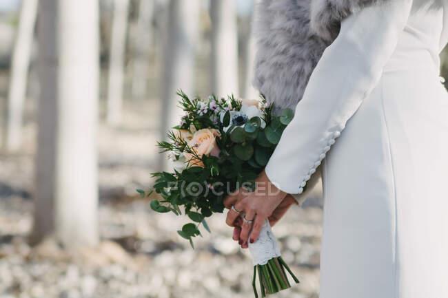 Vista lateral da noiva anônima em casaco branco carregando um monte de flores no fundo borrado de árvores no dia ensolarado — Fotografia de Stock