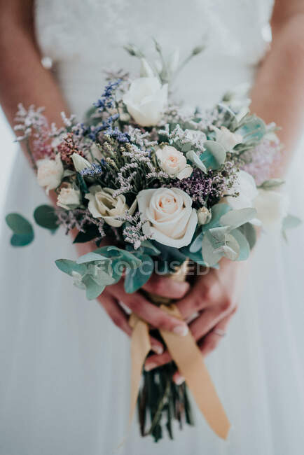 Crop bride with bouquet in forest — Stock Photo