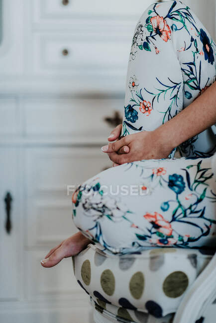 Anonymous barefoot lady in floral pants embracing leg and sitting on comfortable armchair against cabinet in cozy room — Stock Photo