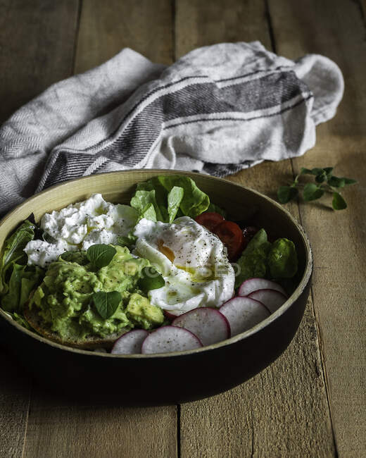 From above delicious fresh elegant avocado dish with egg and vegetables in bowl served on wooden board table with towel — Stock Photo