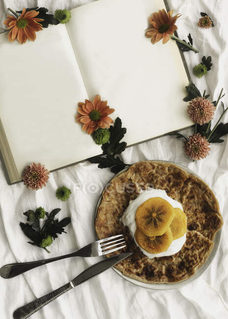 Top view of homemade crepes with cream and sliced persimmon served on plate with knife and fork on surface decorated with white cloth and flowers next to open book with empty pages — стоковое фото